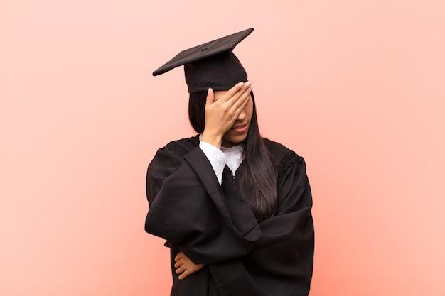 Jonge latijnse studente die gestrest, beschaamd of boos kijkt, met hoofdpijn, kegelvormig gezicht met de hand
