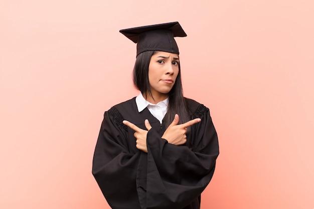 Jonge latijnse studente die verward en verward, onzeker kijkt en in tegengestelde richtingen met twijfel richt