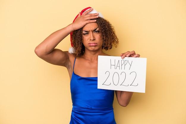 Jonge latijnse transseksuele vrouw die nieuwjaar viert geïsoleerd op gele achtergrond is geschokt, ze herinnert zich een belangrijke vergadering.