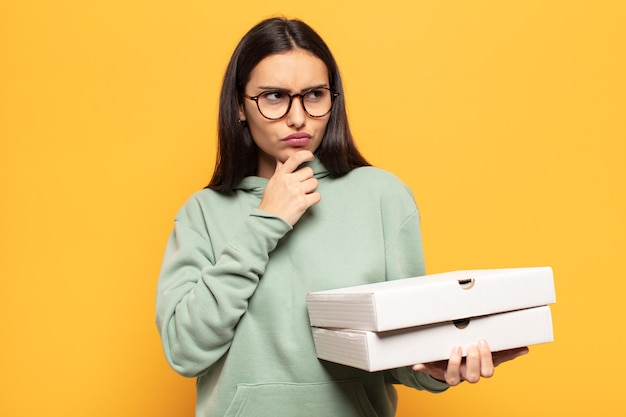 Jonge latijnse vrouw denkt, voelt zich twijfelachtig en verward, met verschillende opties, zich afvragend welke beslissing ze moet nemen