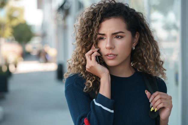 Jonge latijnse vrouw die aan de telefoon praat terwijl ze buiten op straat loopt. stedelijk begrip.