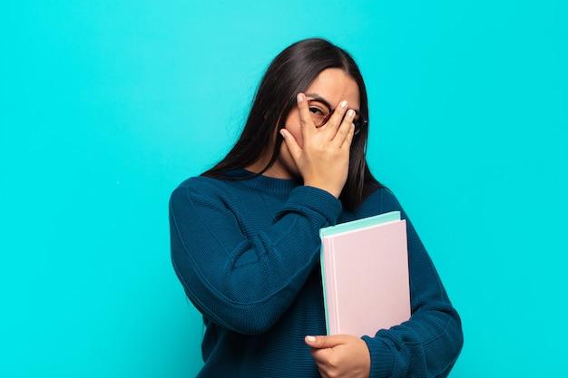 Jonge latijnse vrouw die bang of beschaamd voelt, gluurt of spioneert met ogen half bedekt met handen
