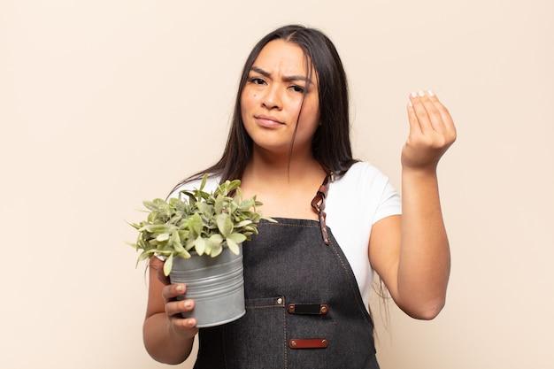 Jonge latijnse vrouw die capice of geldgebaar maakt, die u vertelt uw schulden te betalen!
