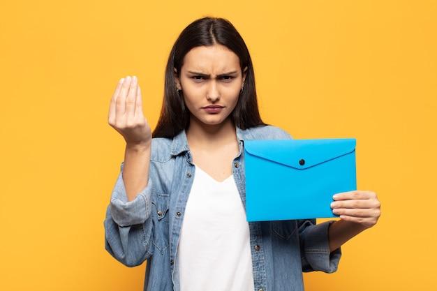 Jonge latijnse vrouw die capice of geldgebaar maakt, die u zegt uw schulden te betalen!