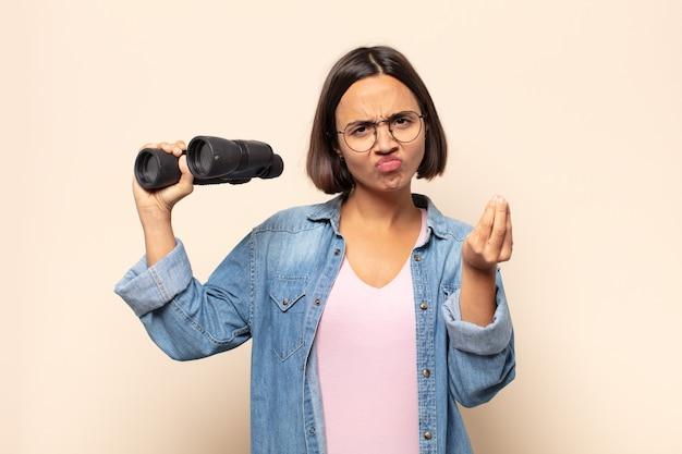 Jonge latijnse vrouw die capice of geldgebaar maakt en je vertelt om je schulden te betalen!