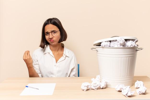 Jonge latijnse vrouw die capice of geldgebaar maakt en u vertelt uw schulden te betalen!