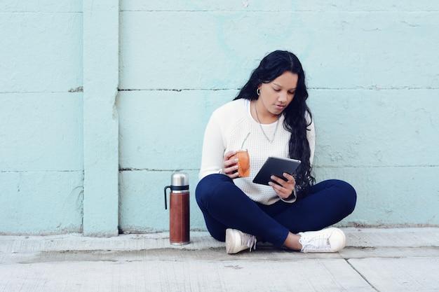 Jonge latijnse vrouw die de traditionele thee van de yerba mate met tablet drinken