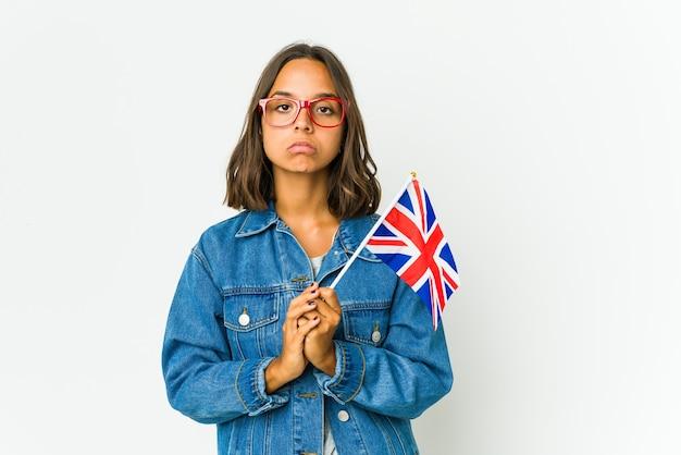 Jonge latijnse vrouw die een engelse vlag houdt die op witte muur wordt geïsoleerd die bidt, toewijding toont, religieus persoon op zoek naar goddelijke inspiratie.