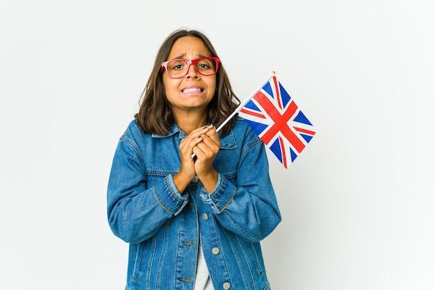 Jonge latijnse vrouw die een engelse vlag houdt die op witte muur wordt geïsoleerd die hand in hand bid dichtbij mond, voelt zich zelfverzekerd.