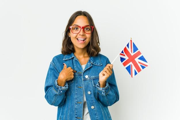 Jonge latijnse vrouw die een engelse vlag op wit houdt verrast wijzend met vinger, breed glimlachend.