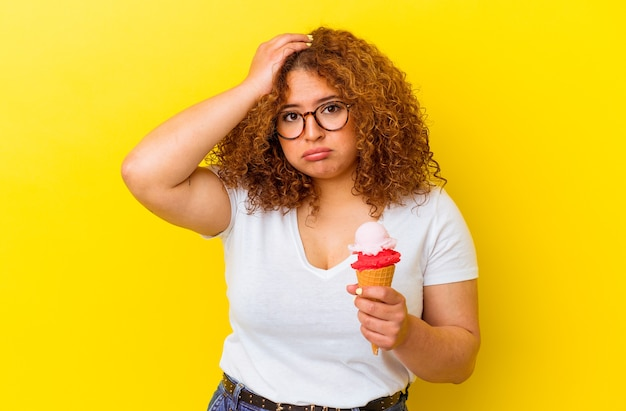 Jonge latijnse vrouw die een ijsje houdt dat op gele achtergrond wordt geïsoleerd die geschokt wordt, heeft zij belangrijke vergadering herinnerd.