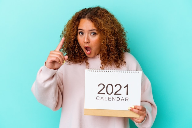 Jonge latijnse vrouw die een kalender houdt die op blauwe achtergrond wordt geïsoleerd die een idee, inspiratieconcept heeft.