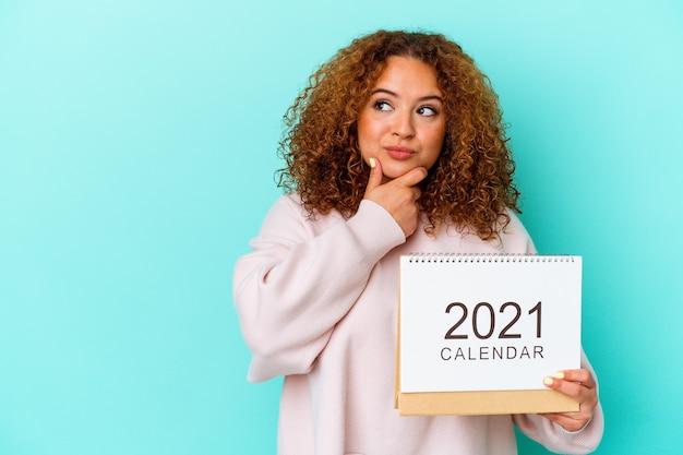 Jonge latijnse vrouw die een kalender houdt die op blauwe achtergrond wordt geïsoleerd die zijwaarts met twijfelachtige en sceptische uitdrukking kijkt.