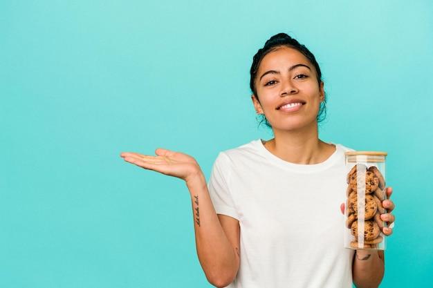 Jonge latijnse vrouw die een koekjeskruik houdt die op blauwe achtergrond wordt geïsoleerd die een exemplaarruimte op een palm toont en een andere hand op taille houdt.