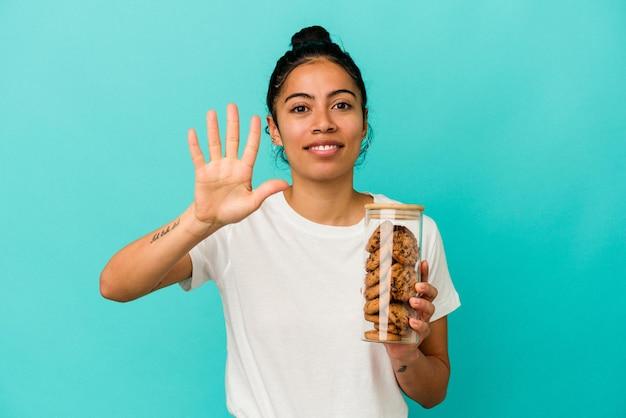 Jonge latijnse vrouw die een koekjeskruik houdt die op blauwe achtergrond wordt geïsoleerd die vrolijk glimlachen toont nummer vijf met vingers.