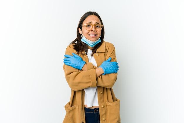 Jonge latijnse vrouw die een masker draagt om te beschermen tegen covid geïsoleerd op een witte muur die koud wordt als gevolg van lage temperatuur of een ziekte.