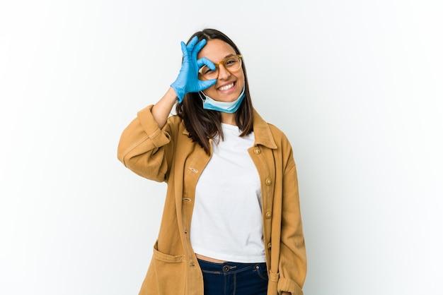 Jonge latijnse vrouw die een masker draagt om tegen covid te beschermen die op witte opgewekte muur wordt geïsoleerd die ok gebaar op oog houdt