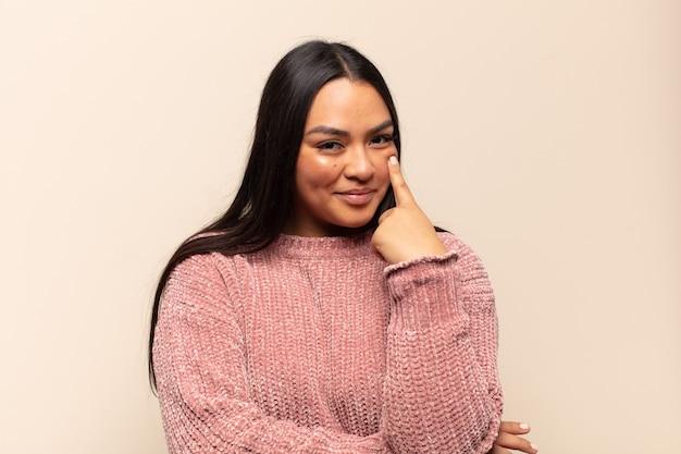 Jonge latijnse vrouw die een oogje in het zeil houdt, niet vertrouwt, toekijkt en alert en waakzaam blijft