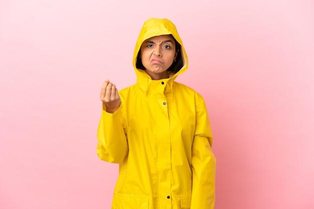 Jonge latijnse vrouw die een regenbestendige jas draagt over een geïsoleerde achtergrond die italiaans gebaar maakt