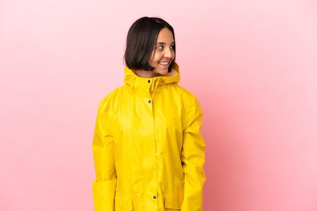Jonge latijnse vrouw die een regenbestendige jas draagt over een geïsoleerde achtergrond die naar de zijkant kijkt