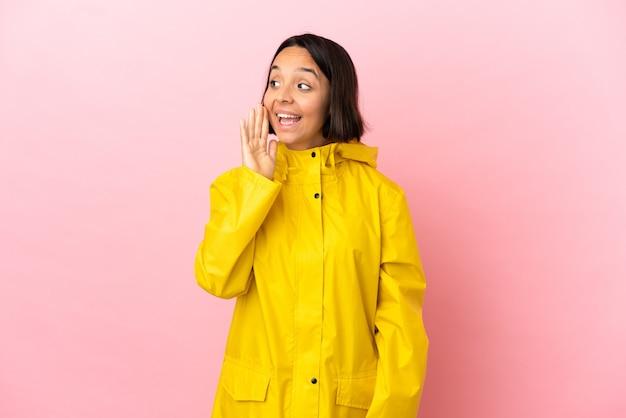 Jonge latijnse vrouw die een regenbestendige jas draagt over een geïsoleerde achtergrond die schreeuwt met wijd open mond naar de zijkant