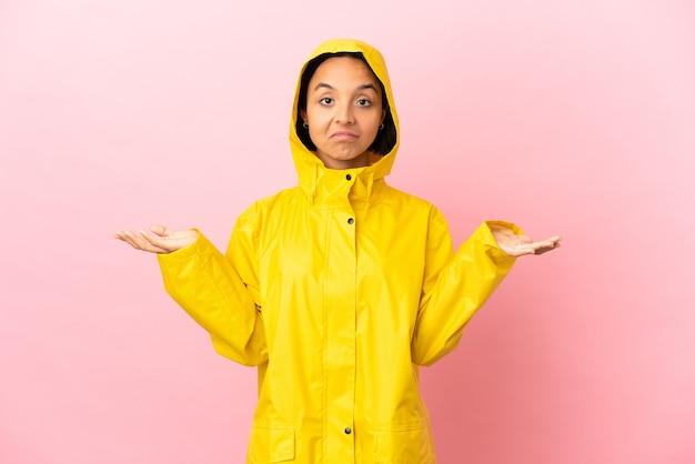 Jonge latijnse vrouw die een regenbestendige jas draagt over een geïsoleerde achtergrond die twijfels heeft