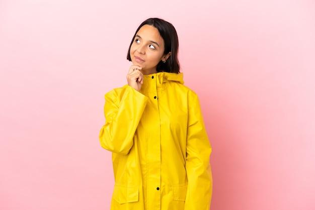Jonge latijnse vrouw die een regenbestendige jas draagt over een geïsoleerde achtergrond en omhoog kijkt