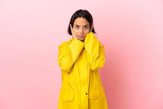 Jonge latijnse vrouw die een regenbestendige jas draagt over een geïsoleerde achtergrond, gefrustreerd en oren bedekt