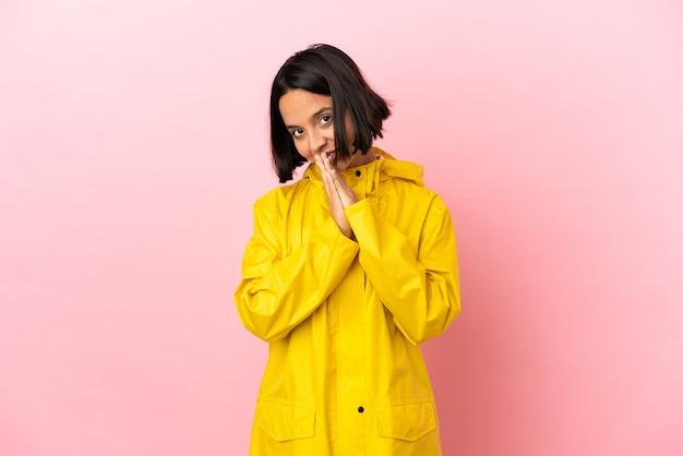 Jonge latijnse vrouw die een regenbestendige jas draagt over een geïsoleerde achtergrond houdt de palm bij elkaar. persoon vraagt om iets