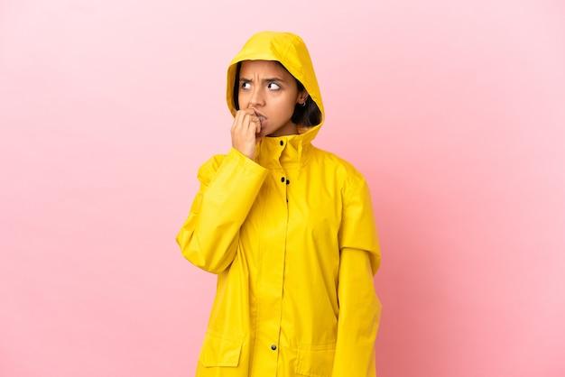 Jonge latijnse vrouw die een regenbestendige jas draagt over een geïsoleerde achtergrond is een beetje nerveus