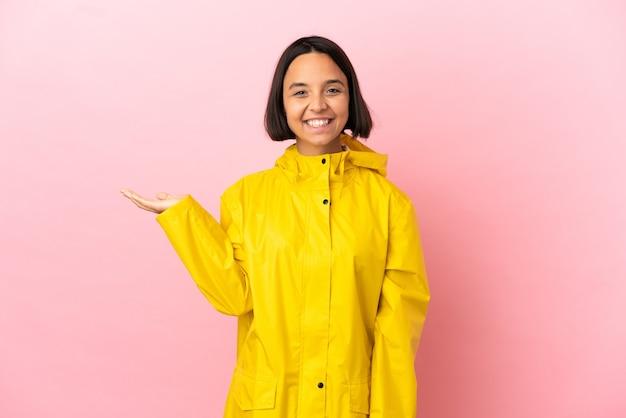 Jonge latijnse vrouw die een regenbestendige jas draagt over een geïsoleerde achtergrond met een denkbeeldige kopie op de handpalm om een advertentie in te voegen