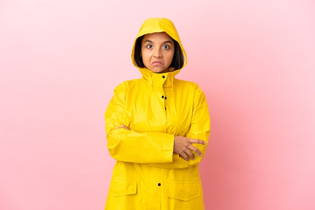 Jonge latijnse vrouw die een regendichte jas draagt over een geïsoleerde achtergrond die twijfels maakt terwijl ze de schouders opheft