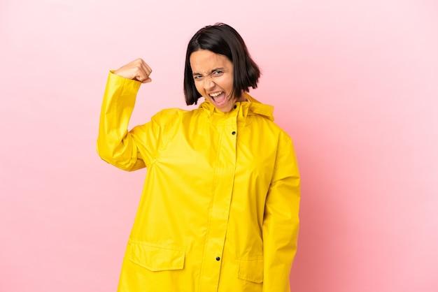 Jonge latijnse vrouw die een regendichte jas draagt over geïsoleerde achtergrond die een overwinning viert