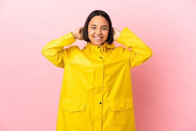 Jonge latijnse vrouw die een regendichte jas draagt over geïsoleerde achtergrond lachen