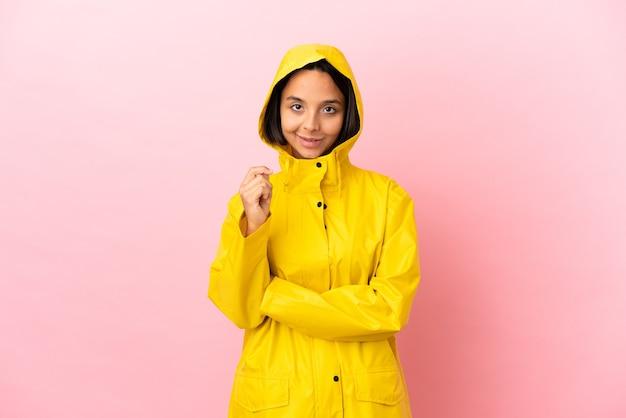 Jonge latijnse vrouw die een regendichte jas draagt over geïsoleerde achtergrond lachend
