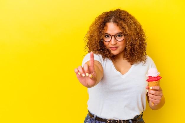 Jonge latijnse vrouw die een roomijs houdt dat op gele achtergrond wordt geïsoleerd die nummer één met vinger toont.