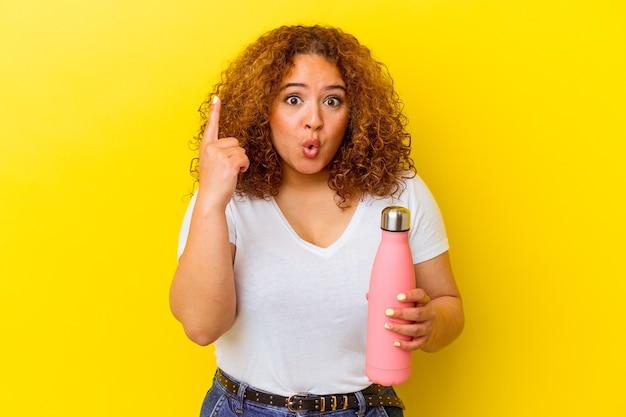 Jonge latijnse vrouw die een thermosfles houdt die op gele achtergrond wordt geïsoleerd die één of ander geweldig idee, concept van creativiteit heeft.