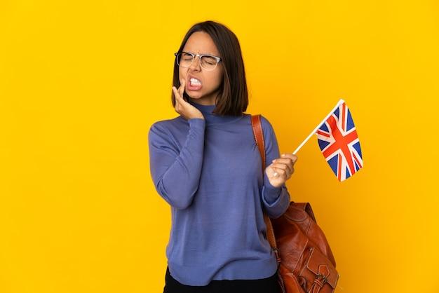 Jonge latijnse vrouw die een vlag van het verenigd koninkrijk houdt die op gele achtergrond met kiespijn wordt geïsoleerd