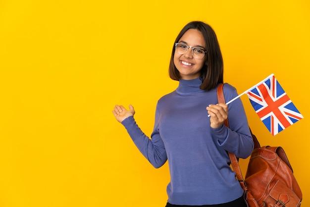 Jonge latijnse vrouw die een vlag van het verenigd koninkrijk houdt die op gele achtergrond wordt geïsoleerd die handen uitstrekt naar de zijkant om uit te nodigen om te komen
