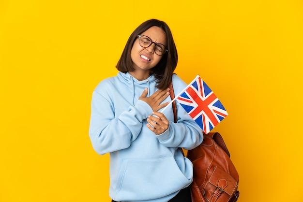 Jonge latijnse vrouw die een vlag van het verenigd koninkrijk houdt die op gele achtergrond wordt geïsoleerd met pijn in het hart
