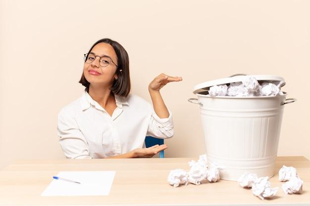 Jonge latijnse vrouw die een voorwerp met beide handen op zijexemplaarruimte houdt, een voorwerp toont, aanbiedt of adverteert
