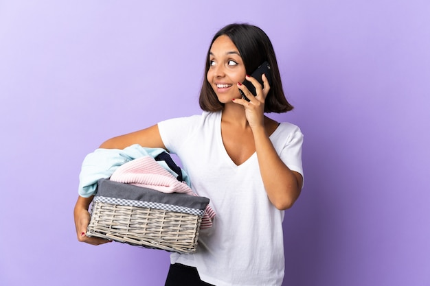 Jonge latijnse vrouw die een wasmand houdt die op paars wordt geïsoleerd die een gesprek met de mobiele telefoon met iemand houdt