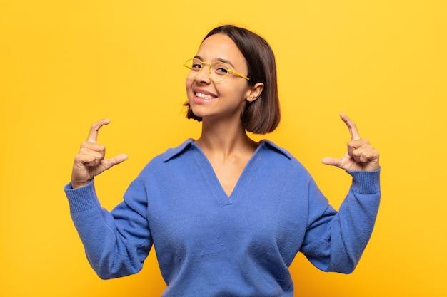 Jonge latijnse vrouw die eigen glimlach met beide handen omlijst of schetst, positief en gelukkig kijkt, wellnessconcept
