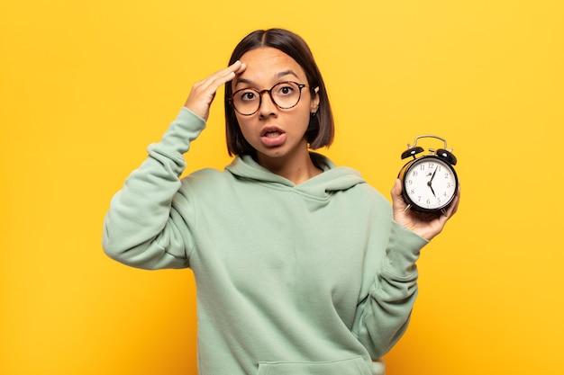 Jonge latijnse vrouw die er blij, verbaasd en verrast uitziet, lacht en zich verbluffend en ongelooflijk goed nieuws realiseert