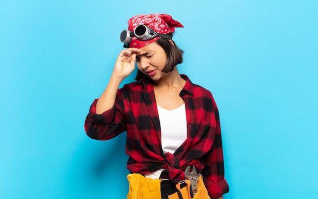 Jonge latijnse vrouw die er gestrest, moe en gefrustreerd uitziet, het zweet van het voorhoofd droogt, zich hopeloos en uitgeput voelt