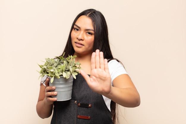 Jonge latijnse vrouw die er serieus, streng, ontevreden en boos uitziet en een open hand laat zien die een stopgebaar maakt