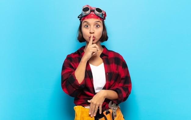 Jonge latijnse vrouw die er serieus uitziet en kruist met de vinger tegen de lippen gedrukt die stilte of stilte eist