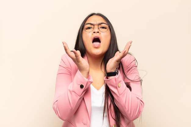 Jonge latijnse vrouw die er wanhopig en gefrustreerd, gestrest, ongelukkig en geïrriteerd uitziet, schreeuwend en schreeuwend