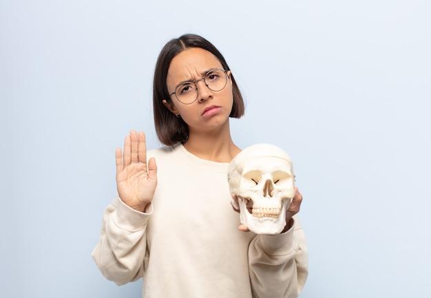 Jonge latijnse vrouw die ernstig, streng, ontevreden en boos kijkt die open palm toont die stopgebaar maakt