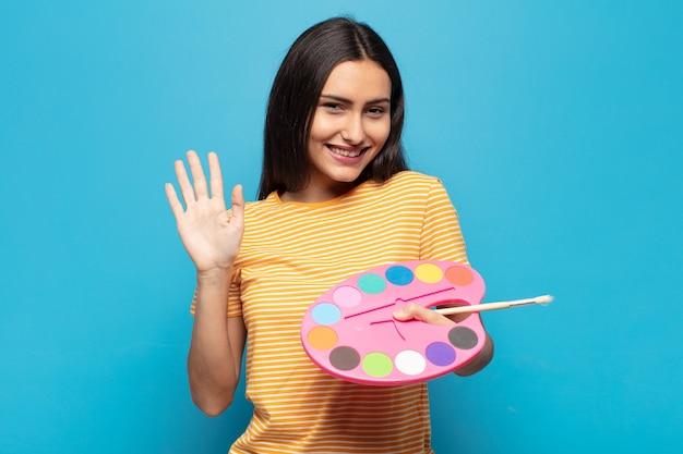 Jonge latijnse vrouw die gelukkig en opgewekt glimlacht, hand zwaait, u verwelkomt en begroet, of afscheid neemt